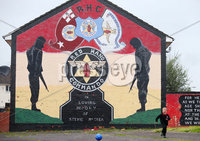 Press Eye Belfast - Northern Ireland 12th September 2017. Loyalist paramilitary group the Red Hand Commando has made an application to be removed from the UK\'s list of proscribed terrorist organisations.  The RHC was formed in 1972 in the Shankill area of west Belfast.  It had close links to the UVF and waged a paramilitary campaign until the loyalist ceasefires of 1994.. A young boy plays football beside a Red Hand Commando mural in the Shankill estate area of west Belfast. . Picture by Jonathan Porter/PressEye.com.