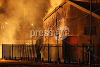 Press Eye - Belfast - Northern Ireland - 11th July  2018 . General view fire officers cooling down a building at the  Hope Street bonfire at Sandy Row in South Belfast.. It comes after the PSNI issued a notice informing the public that paramilitaries intend to orchestrate serious disorder against police officers on the Eleventh night.. Photo by Kelvin Boyes / Press Eye..
