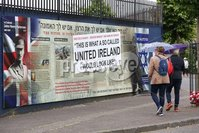 PressEye - Belfast - Northern Ireland - 13th June 2018. Murals on Beverly Street and Northumberland Street in the Greater Shankill area have been damaged in arson attacks. . They depict scenes of the role Polish airmen played in the Battle of Britain and history of Lt Colonel John Henry Patterson and the First World War.. Pictured: Tourists walk around the murals which were damaged.. Picture: Philip Magowan / PressEye