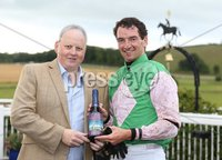 Press Eye - Belfast - Northern Ireland - 13th July 2017 . Downpatrick racecourse family fun race day.. TWO N & M\'S FLAT RACE . Peter Magill from Downpatrick racecourse presents race winner Paddy Mullins with his prize. Picture by Matt Mackey / presseye.com.