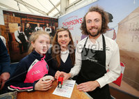 Press Eye - Belfast - Northern Ireland - 15th May 2019. First day of the Balmoral Show, in partnership with Ulster Bank.  Pictured at Balmoral Park, outside Lisburn, is (L-R) Leanne(13) and her mother Ann Marie Laverty from Mayobridge, Co. Down, with Thompson\'s Teas Jamie Thompson.  The mother and daughter were getting their Ulster Bank Food Trail card stamped.  Customers can visit different stands in the food hall getting their cards stamp which can be entered into a free draw. . . Picture by Jonathan Porter/PressEye. .