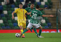 Press Eye-Belfast-Northern Ireland -18th November 2020. National Football Stadium at Windsor Park, Belfast. . 18/11/2020. Northern Ireland  Josh Magennis    and Craig Cathcart  Romania Ionut Nedelcearu   during Wednesday   night\'s UEFA Nations League match at the National Football Stadium at Windsor Park,Belfast.. Mandatory Credit PressEye