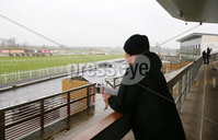 Press Eye - Belfast - Northern Ireland - 17th March 2020. As cases of coronavirus infections increase across Northern Ireland business and organisations are closing and taking action for social distancing. . St Patricks Day racing went ahead at Down Royal behind closed doors with only jockeys and officials allowed at the track.  A trainer watches from an empty grandstand as the third race - The Cleary Contracting Ltd Novice Handicap Hurdle - gets under way. . Picture by Jonathan Porter/PressEye