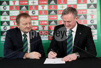 Press Eye - Belfast -  Northern Ireland - 09th February 2018 - Photo by William Cherry/Presseye. Michael O'Neill signs the four-year contract extension, which will see him continue as Northern Ireland senior men's international manager until 2024, as Irish FA President David Martin looks on.