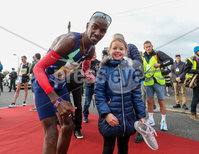Press Eye - Belfast - Northern Ireland - 12th September 2020 . P&O Antrim Coast Half Marathon.. Athletics fans where in for a treat on Saturday when Sir Mo Farah ran and won the P&O Antrim Coast Half Marathon.. Mia Duddy (8) gets her trainers signed by Sir Mo.. Photo by Matt Mackey / Press Eye.